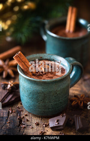 Hot chocolate with a cinnamon stick, anise star and grated chocolate topping in festive Christmas setting on dark - Stock Photo