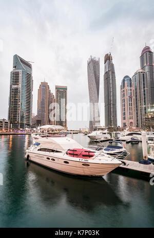 Yacht in front of skyscrapers, Dubai Marina, Dubai, United Arab Emirates - Stock Photo