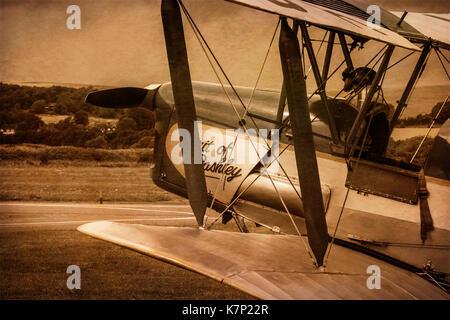 Sepia image of a De Havilland DH82A Tiger Moth on an airfield - Stock Photo