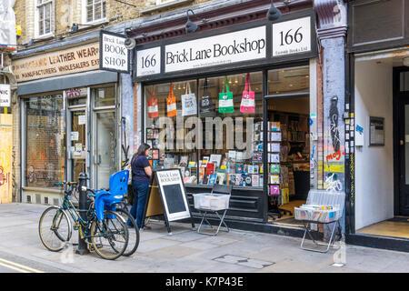 Woman browsing in the window of the Brick Lane Bookshop in Whitechapel. - Stock Photo