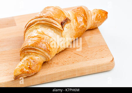 Croissant on wooden plate. white background. Top view. - Stock Photo