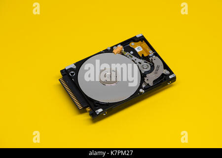 Close-up of an opened computer hard drive disk on yellow colored background. Read-write head retracted. - Stock Photo
