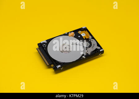 Close-up of an opened computer hard drive disk on yellow colored background. - Stock Photo