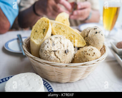 bread basket on a table with a selection of bread. Olive bread rolls and garlic bread baguette sliced. Goats cheese - Stock Photo