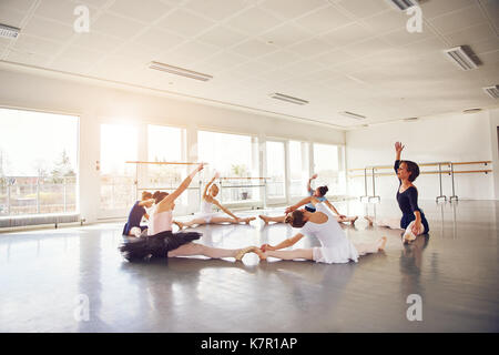Little ballerinas sitting and doing string exercise with teacher in ballet class. - Stock Photo
