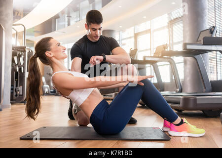 Personal trainer timing young fit woman during isometric exercis - Stock Photo