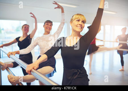 Cheerful adult ballerinas performing ballet in class together and posing with hands up. - Stock Photo