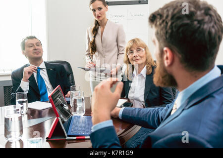 Happy middle-aged managers listening to their younger colleague  - Stock Photo