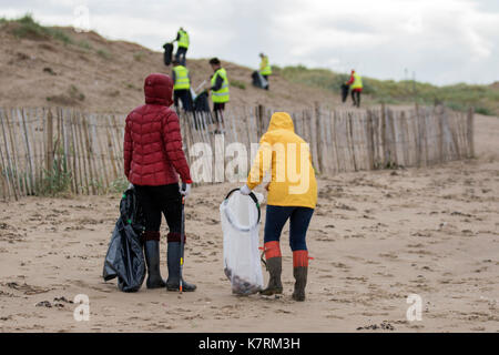Crosby, Merseyside.  UK Weather.  17th September, 2017. Elmo & Flow, both 6 years old, on National Beach Clean Day as volunteers Friends of Crosby beach gather to collect plastic, rubber, litter and other debris brought in by the tide. from the coastal beaches in the Mersey estuary. Squads of volunteer pickers met on Marine Way as part of the Great British Beach Clean and litter surveying event on the coasts of Britain cleaning up the garbage that has washed up on shore. Credit; MediaWorldImages/AlamyLiveNews.