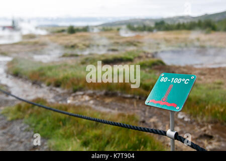 Sign warning of high temperature of the thermal waters of the Geysir area in Iceland. - Stock Photo