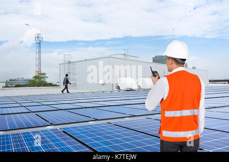 Engineer on factory roof checking solar panels - Stock Photo
