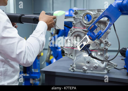 Engineer and assistant robot working with 3D portable measuring scan automotive part in factory, Industry 4.0 concept - Stock Photo