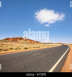 Long curving road stretching into the distance in the Pilbara region of Western Australia, under blue sky with single - Stock Photo