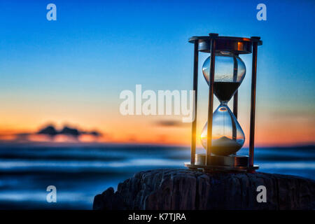 Hourglass or sand timer in front of a beatiful clear sunrise or sunset. - Stock Photo