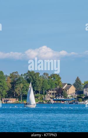 Sailboater enjoys a beautiful late summer day on Lake Couchiching near Orillia Ontario. - Stock Photo