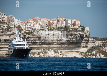 Panoramic view of Bonifacio city and cliffs with motor yacht on anchor, Corsica island, France - Stock Photo
