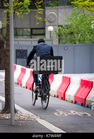 UberEATS cycle delivery courier in London, Ubereats is a take away food service which can be ordered from a Smartphone - Stock Photo