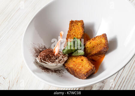 Carrot cake and fresh carrot on wooden table - Stock Photo