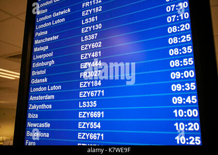 airport flight information screen showing destinations low cost airline codes and flight times - Stock Photo