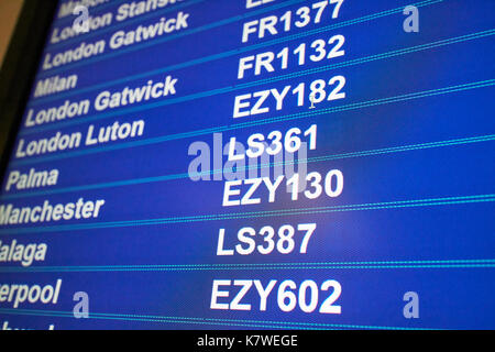 airport flight information screen showing destinations low cost airline codes for easyjet ryanair and jet2 - Stock Photo