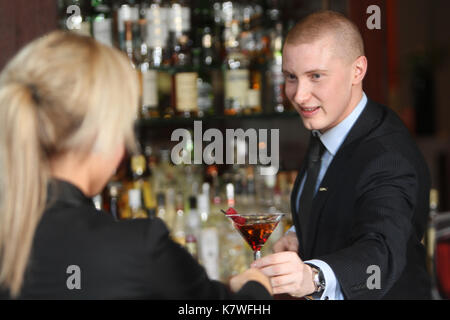 Barman serving cocktail to customer in Hotel bar - Stock Photo