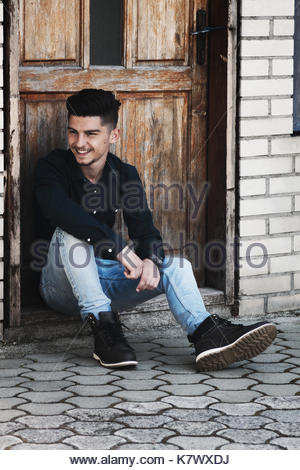 smiling young man sitting on threshold and watching sideways - Stock Photo
