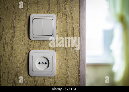Wall Plastic electrical outlet and switch closeup. - Stock Photo