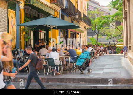 Valencia Spain street, people relax over lunch at street cafes sited near the Mercado Central in the old town - - Stock Photo