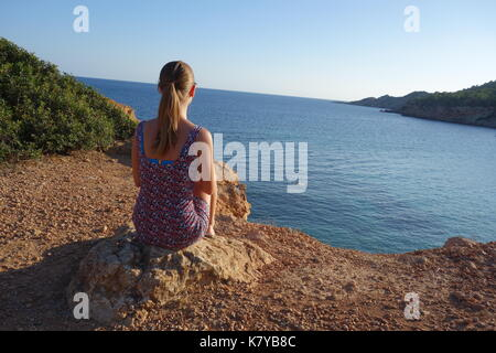 Blonde girl looking towards the beach of Cala sa Caleta or Bol Nou, Spain - Stock Photo