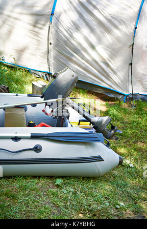 Fishing inflatable boat with a motor on the background of the tent - Stock Photo