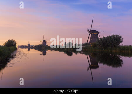 Windmills of Kinderdijk, a world heritage site of UNESCO, are lined up at the waterside at sunset. Besides windmills, - Stock Photo