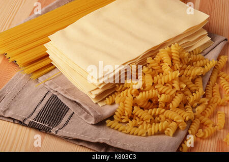 Assorted types of pasta on wooden background. Various forms of pasta, spaghetti, lasagna sheets and fusilli. - Stock Photo