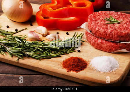 Raw ground beef burgers cutlets with red onion, garlic, olive and red pepper oil to prepare for frying in oven, - Stock Photo