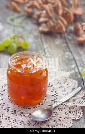 Slatko - white grape jam (sweet), traditional serbian desert; white grapes in syrup in a glass jar - Stock Photo