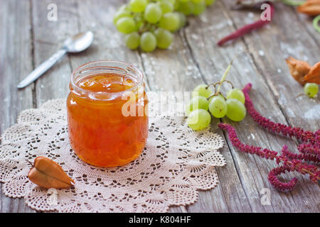 Slatko - preserved white grapes in glass jar, on wooden background; traditional serbian desert of white grapes or - Stock Photo