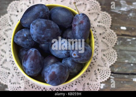 Top view of plums in yellow bowl, on wooden background - Stock Photo