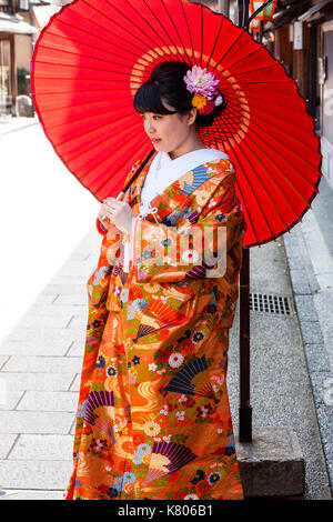 Japan, Kanazawa, Higashi Chaya. Side-view Japanese young women standing in kimono and holding big red parsole. Flowers - Stock Photo
