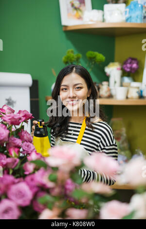 Young beautiful asian girl florist taking care of flowers at workplace. - Stock Photo