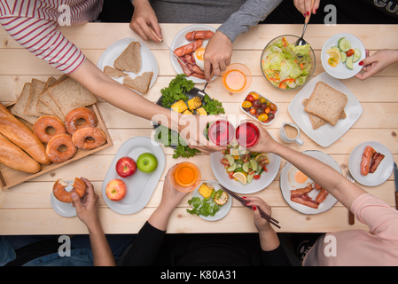 Enjoying dinner with friends.  Top view of group of people having dinner together while sitting at wooden table - Stock Photo