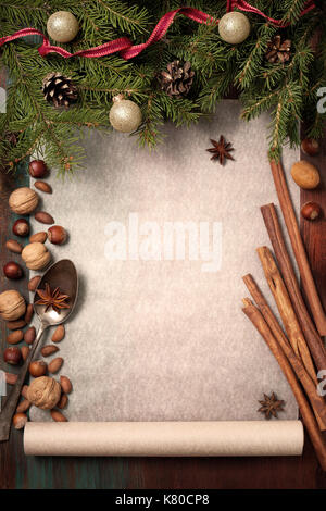 Christmas background with ingredients for baking: cinnamon, star anise, walnuts, hazelnuts, baking paper. (view - Stock Photo
