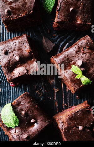 Dark chocolate brownies decorated with mint leaf on dark background. Top view, vertical composition - Stock Photo
