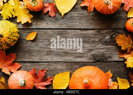 Fallen leaves and pumpkins on wooden background with copy space for text. Top view. Seasonal background for Halloween - Stock Photo
