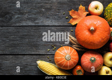 Autumn harvest Thanksgiving pumpkins, apples, corn, wheat ears and fallen leaves on wooden background. Top view - Stock Photo