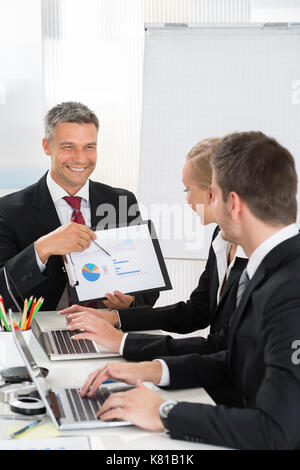 Mature Businessman Explaining Graph To His Co- Workers In Office - Stock Photo