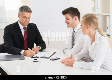 Group Of Businesspeople Discussing On Graph At Desk - Stock Photo