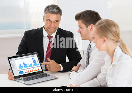 Mature Businessman Showing Graph On Laptop To His Colleagues In Office - Stock Photo