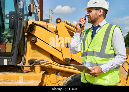 Busy Construction Worker in Suit - Stock Photo