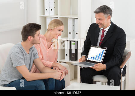 Financial Consultant Showing Graph On Laptop To Happy Young Couple - Stock Photo