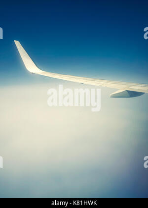 Wing of flying airplane above the clouds into an ethereal atmosphere - Stock Photo