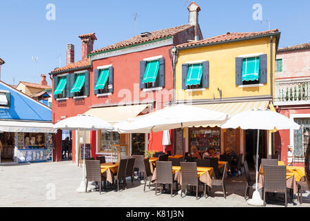 Brightly colored open air restaurant  Burano, Venice, Italy with a few tourists sitting eating in a small square - Stock Photo